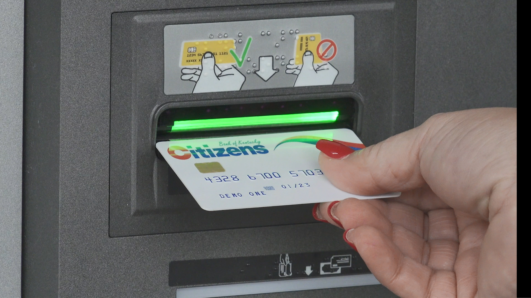 woman inserting card into atm